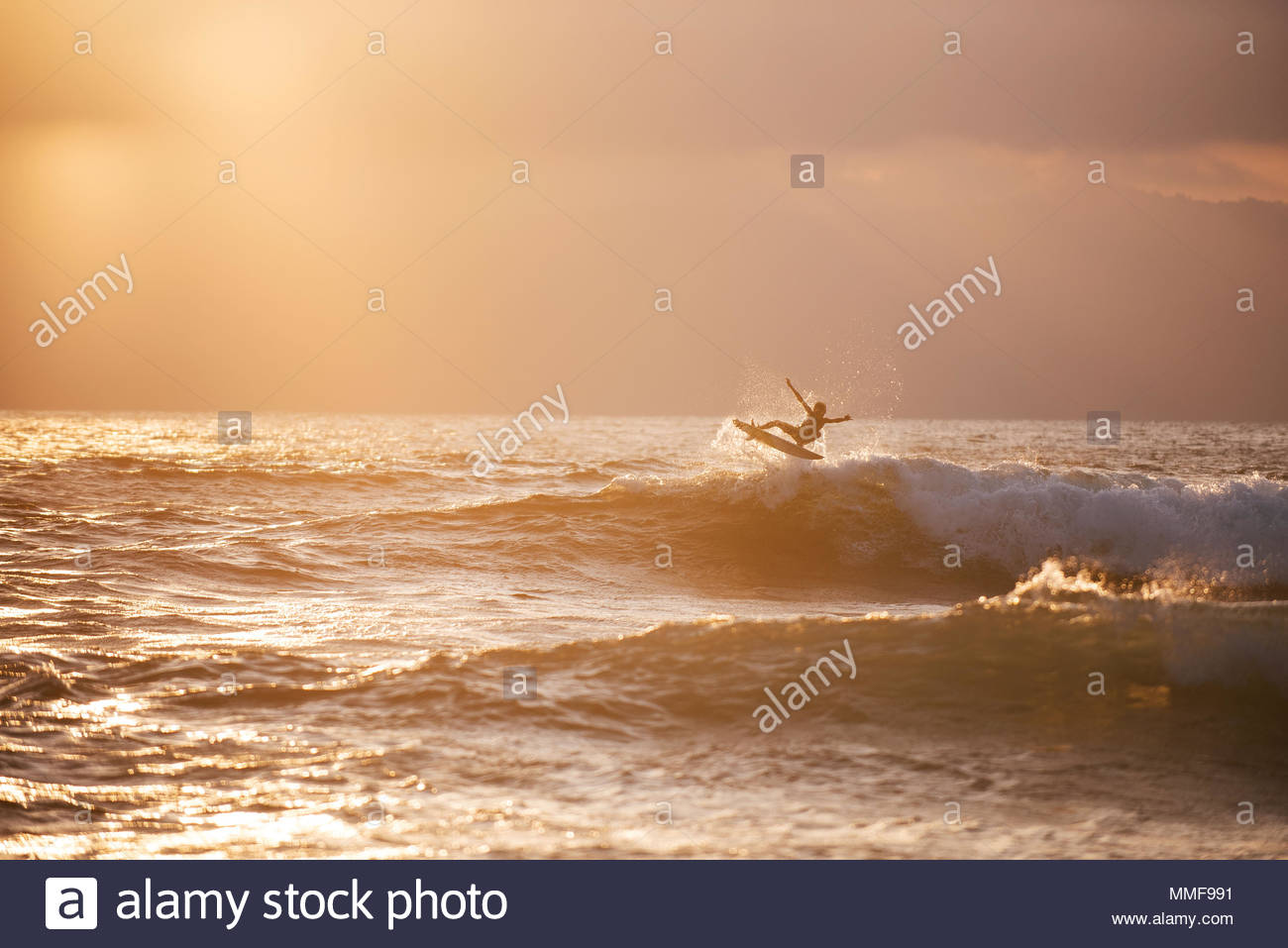 A kid surfer airs out of a little wave at Lakey Peak. - Stock Image