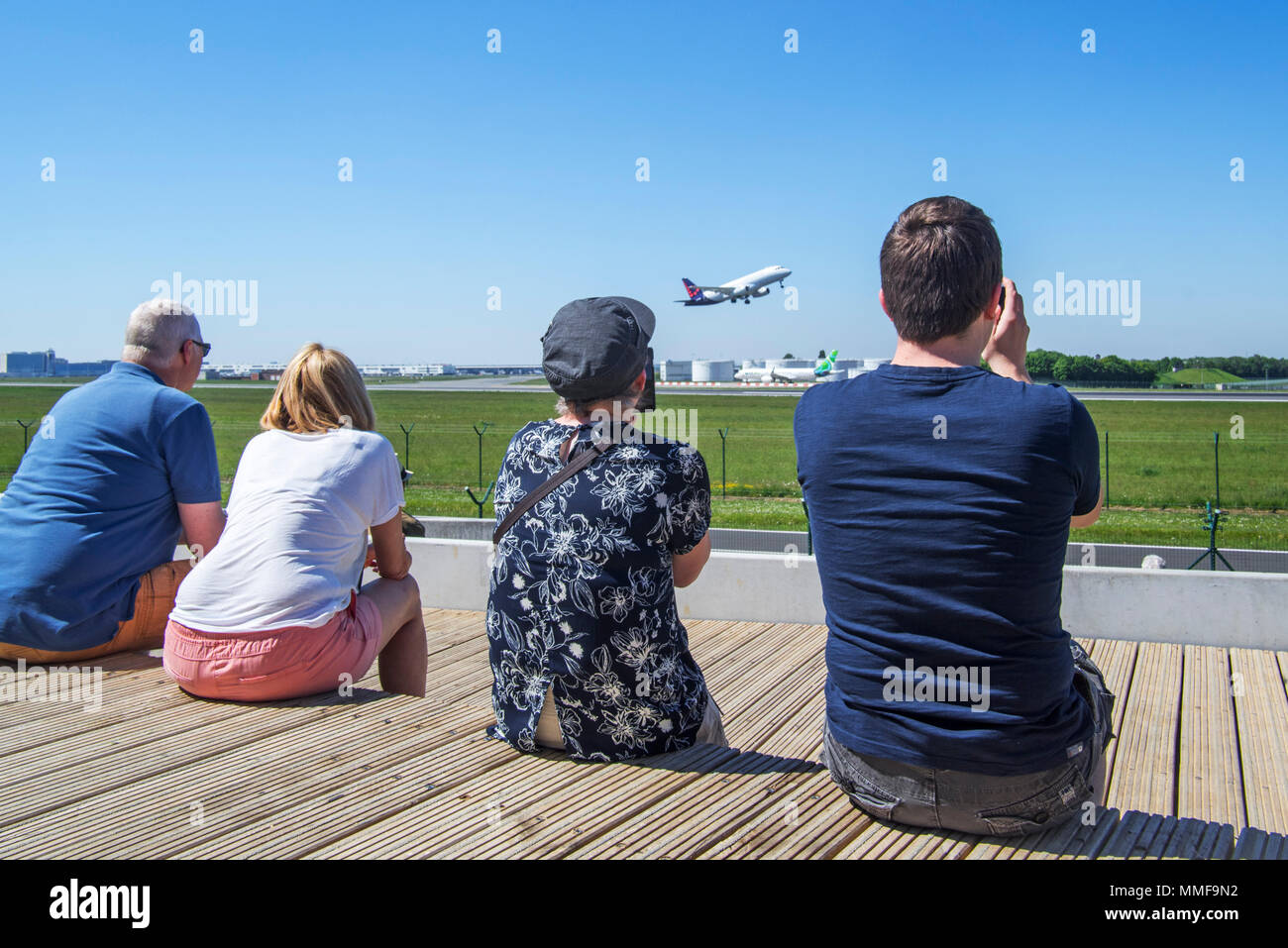 Plane spotters on aircraft spotting platform watching airplane from Brussels Airlines taking off from runway at Brussels Airport, Zaventem, Belgium - Stock Image