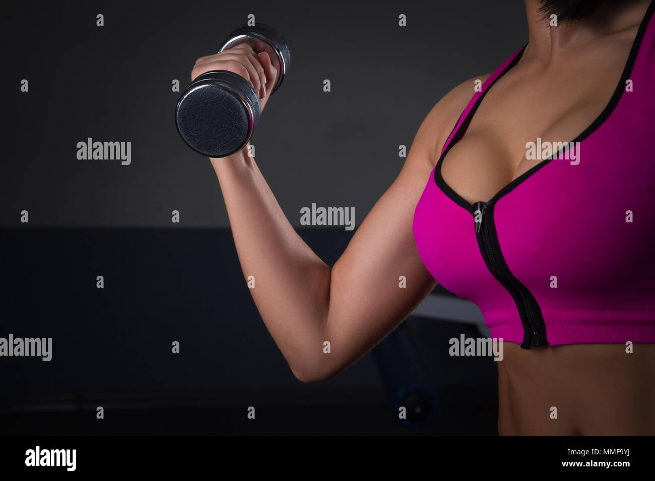 fitness model brunette holding weights on black background. athlete lifts a  dumbbell. halthy concept
