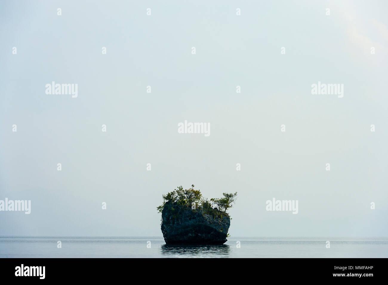 A small limestone island in a dead calm sea. - Stock Image