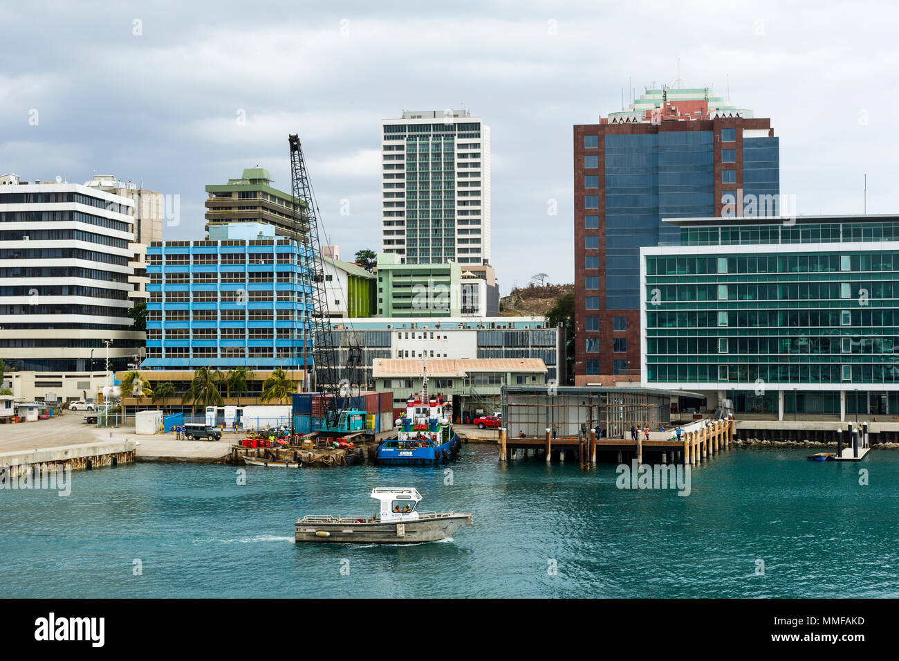 A fishing boat in the harbor beneath the central business district of Port Moresby. - Stock Image