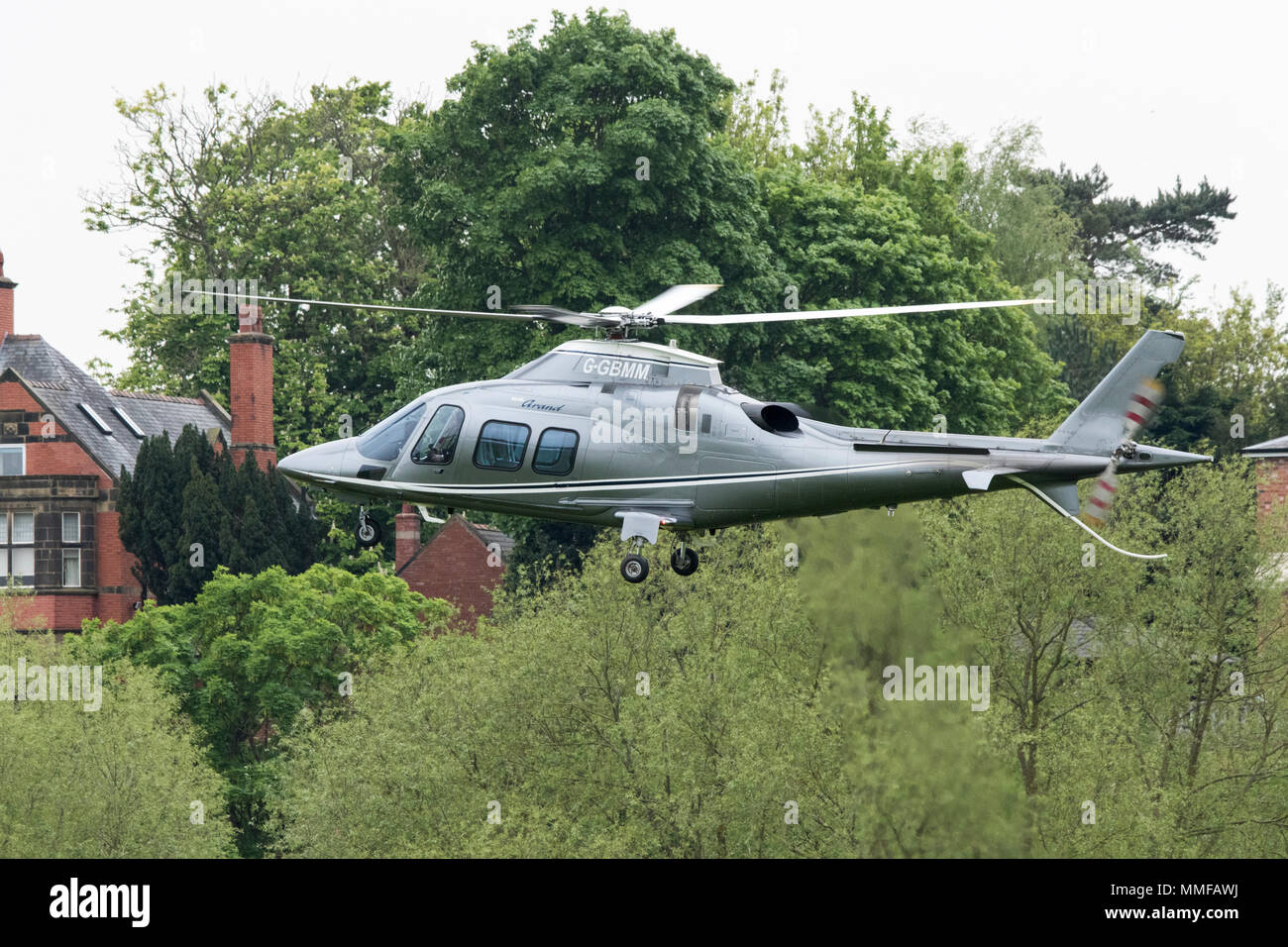 Agusta a.1095 helicopter in flight ascending elevation after landing at chester races - Stock Image