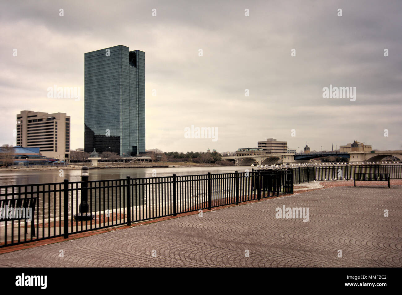 A panoramic view of downtown Toledo Ohio's skyline from across the Maumee River at a popular restaurant area with a paver brick boardwalk. Stock Photo