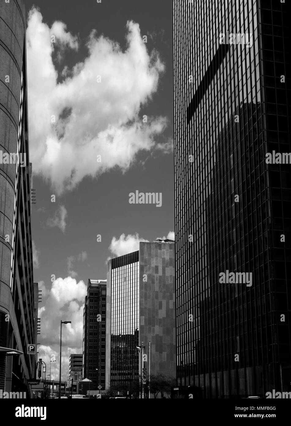 Black and white photo of a typical city street with skyscrapers lining it and cars parked on it. - Stock Image