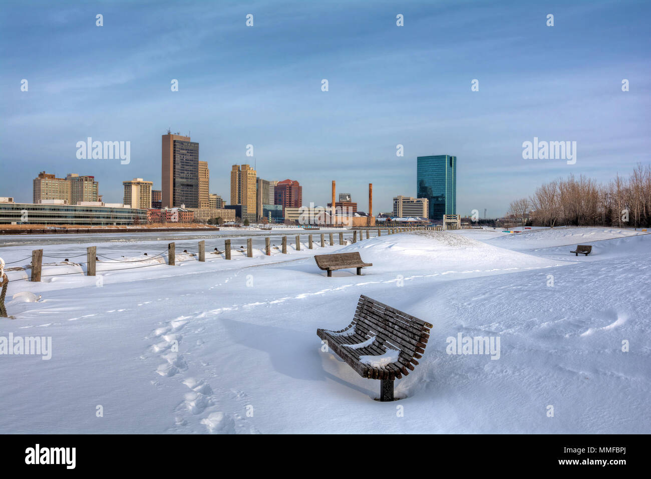 A view of downtown Toledo Ohio's skyline from across the frozen and snow-covered Maumee river a beautiful partly cloudy blue sky. Stock Photo