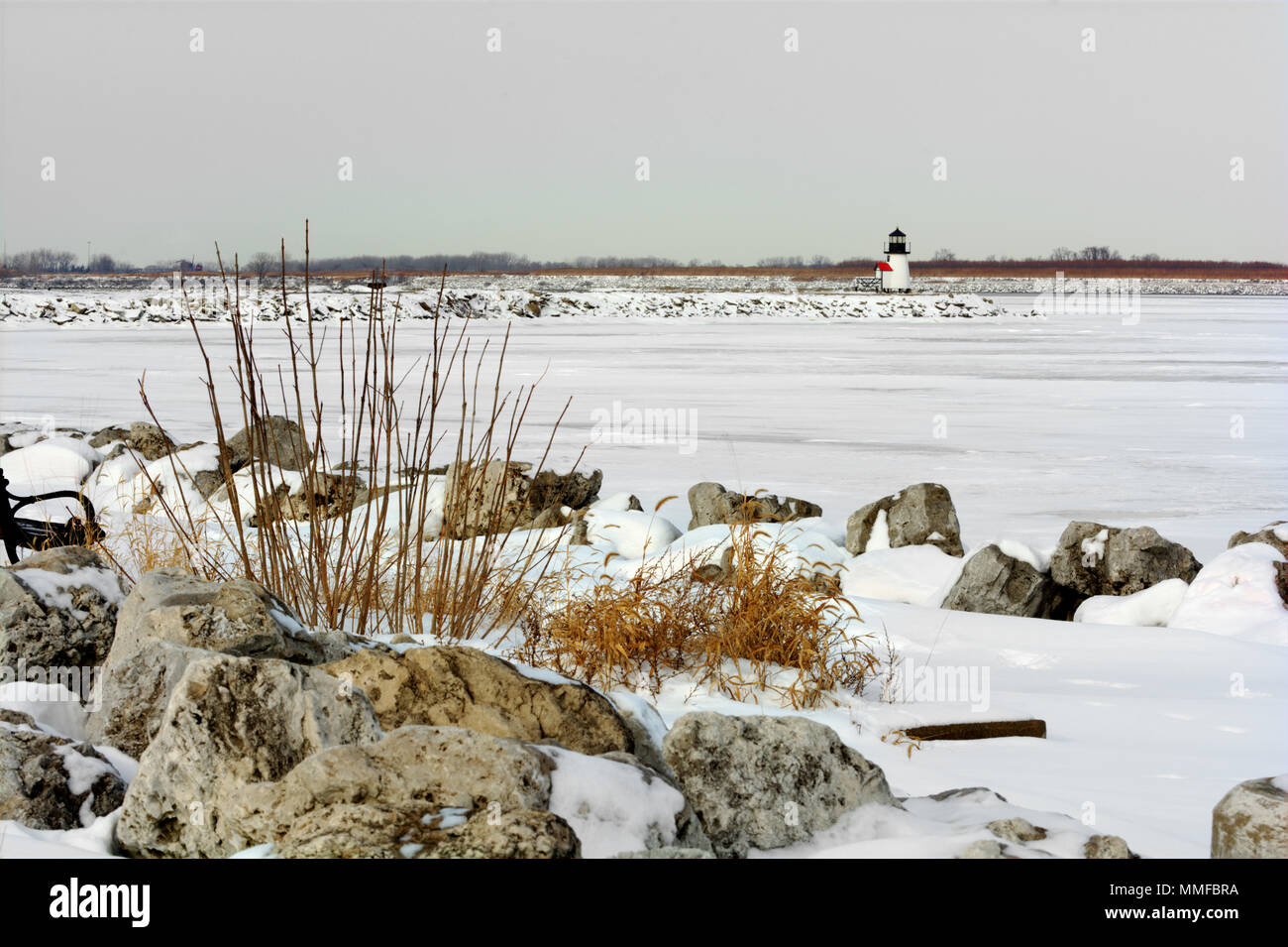 A small lighthouse at the entrance to the port of Toledo Ohio in winter. Lake Erie is frozen and covered with snow in this winter scene. Stock Photo