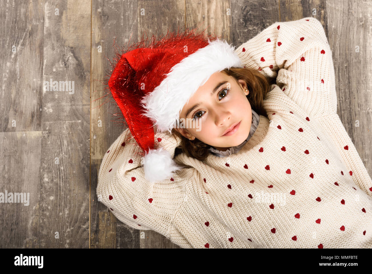 8cc8407ae9f9 Adorable little girl wearing santa hat laying on wooden floor ...