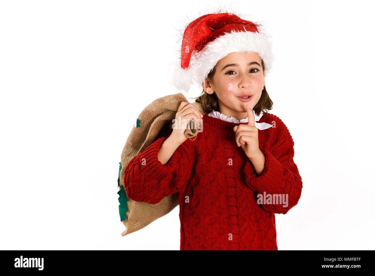 7acbf8702 Adorable little girl wearing santa hat carrying gift bag isolated on ...