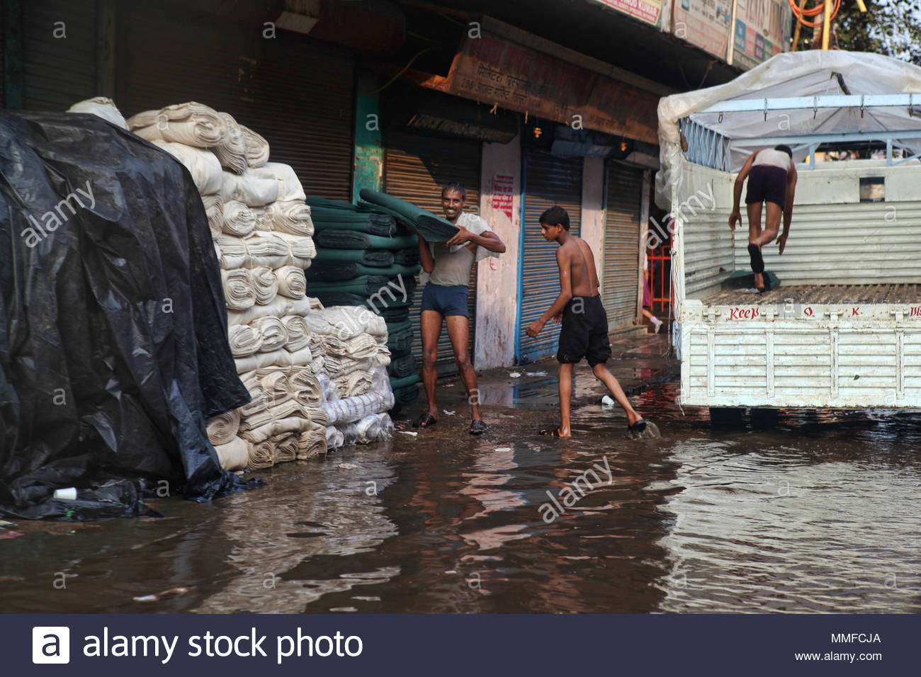 Men load bolts of cloth onto a truck from a flooded street corner during the monsoon season in Delhi. - Stock Image