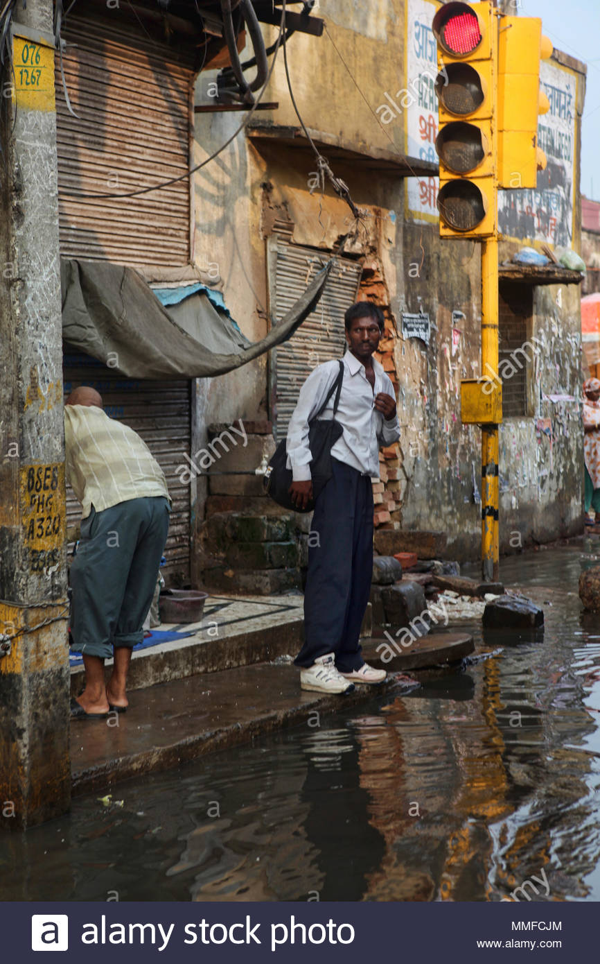 A man stands by a flooded street during the monsoon season in Delhi. - Stock Image