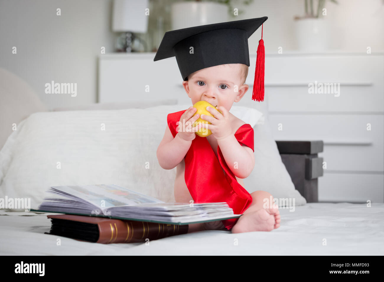 eb1d5db1543 Adorable baby boy in graduation cap sitting on bed with books and biting  apple - Stock