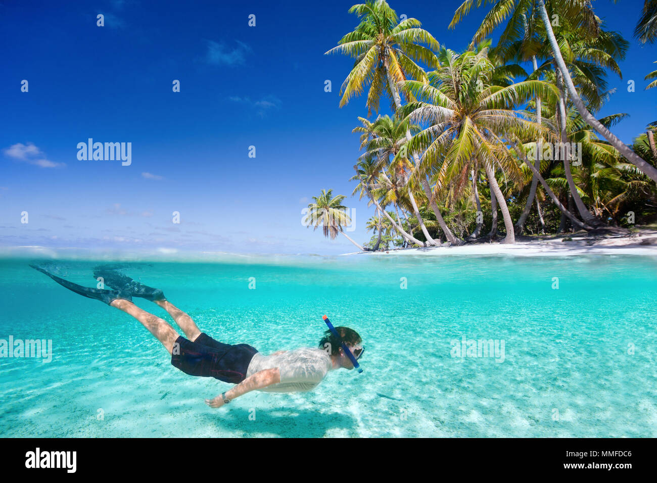 Man swimming in a clear tropical waters in front of exotic island - Stock Image