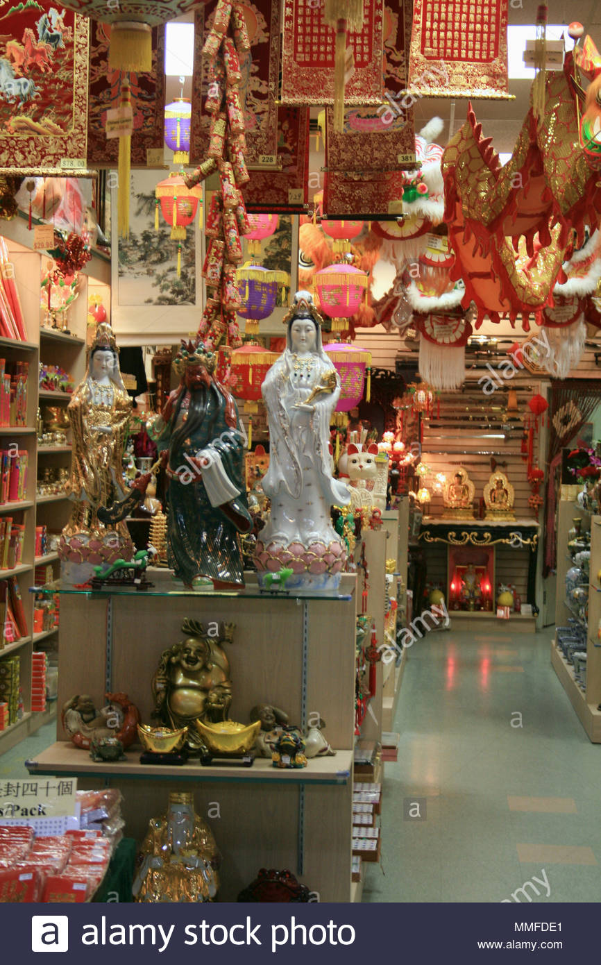 A Chinese shop selling various religious statues and other cultural items. - Stock Image