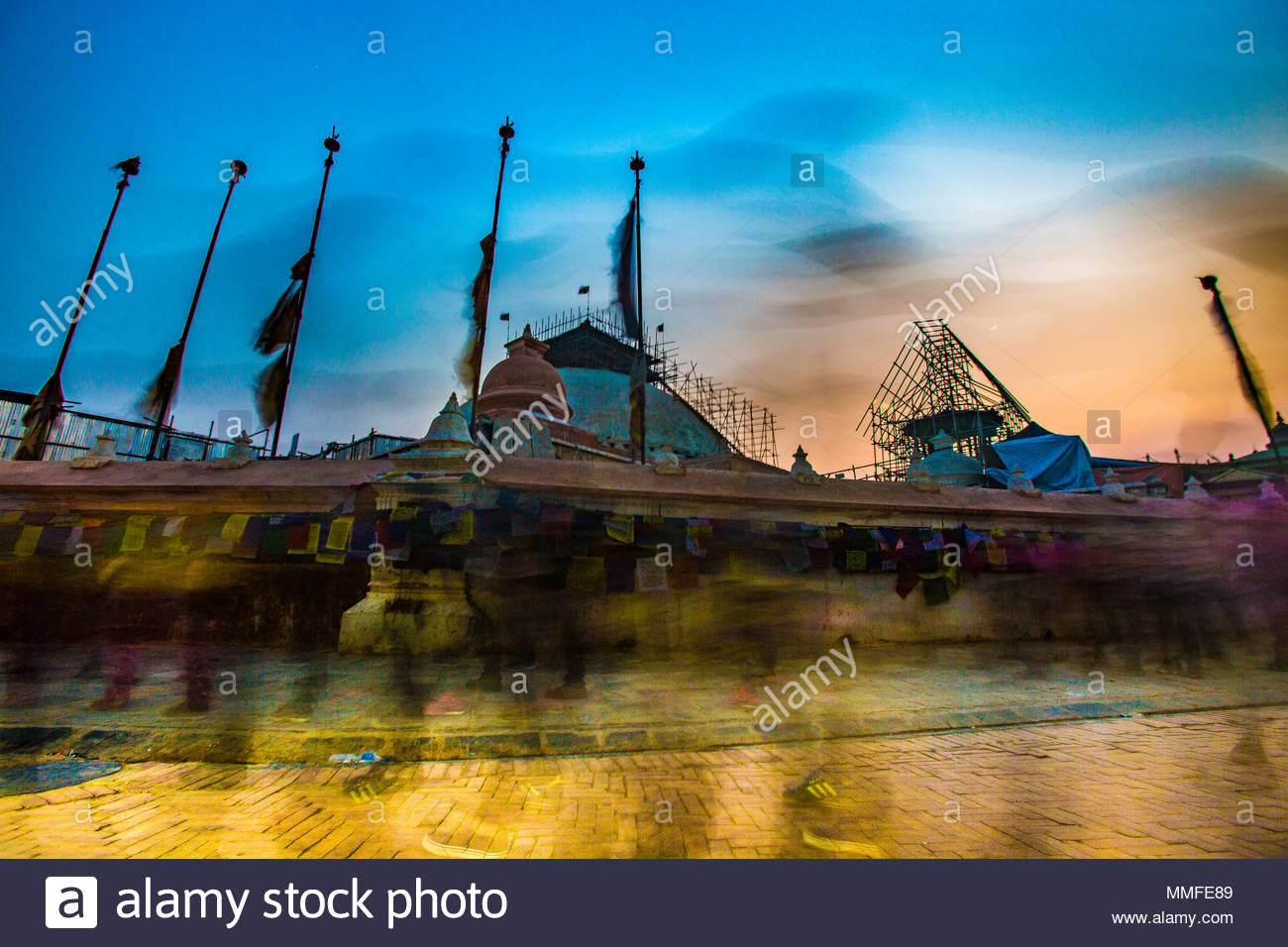Worshipers in blurred swirl encircle a shrine with prayer flags as dusk approaches. - Stock Image