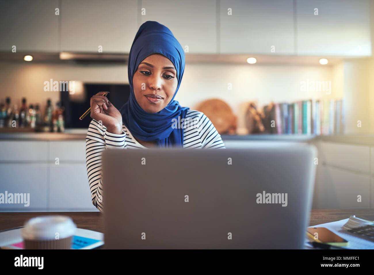 Smiling young Muslim female entrepreneur wearing a hijab sitting at a table in her kitchen writing down notes and working on a laptop Stock Photo