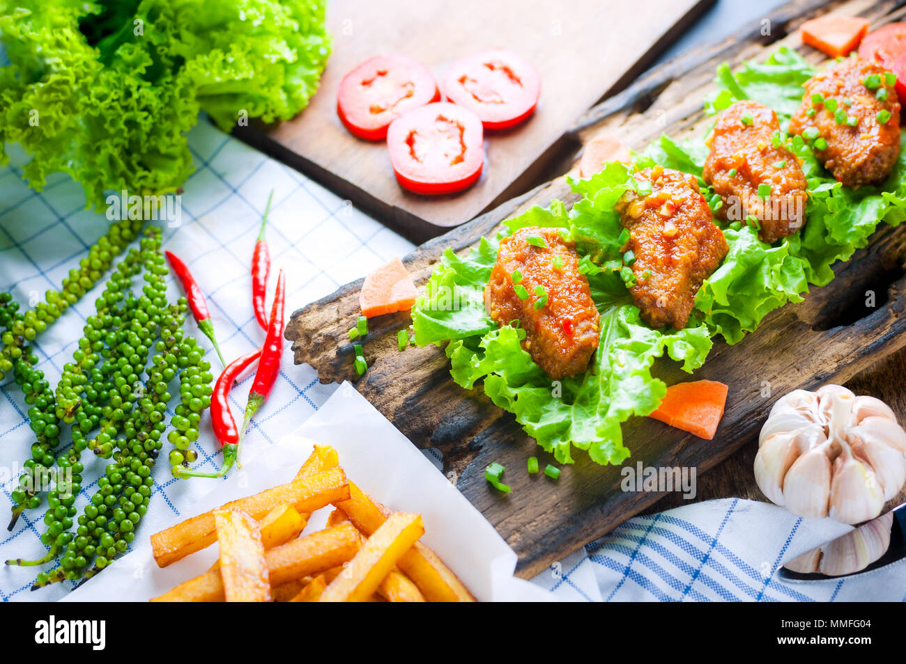 Fried chicken wings with spicy chilli sauce on rustic serving board, herbs and vegetable over wooden background. Stock Photo