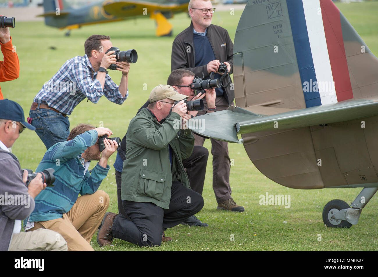 IWM Duxford, Cambridgeshire, UK. 11 May, 2018. Entry level photographers and enthusiasts get to grips with aviation photography on the Airfield at IWM Duxford with a 40s dressed model and Supermarine Spitfire for Best of British day. Photography Days are run at Duxford up to 7 September, themed as best of British, Royal Air Force and US Air Force allowing participants to get up close to aircraft static and flying. Credit: Malcolm Park/Alamy Live News. - Stock Image