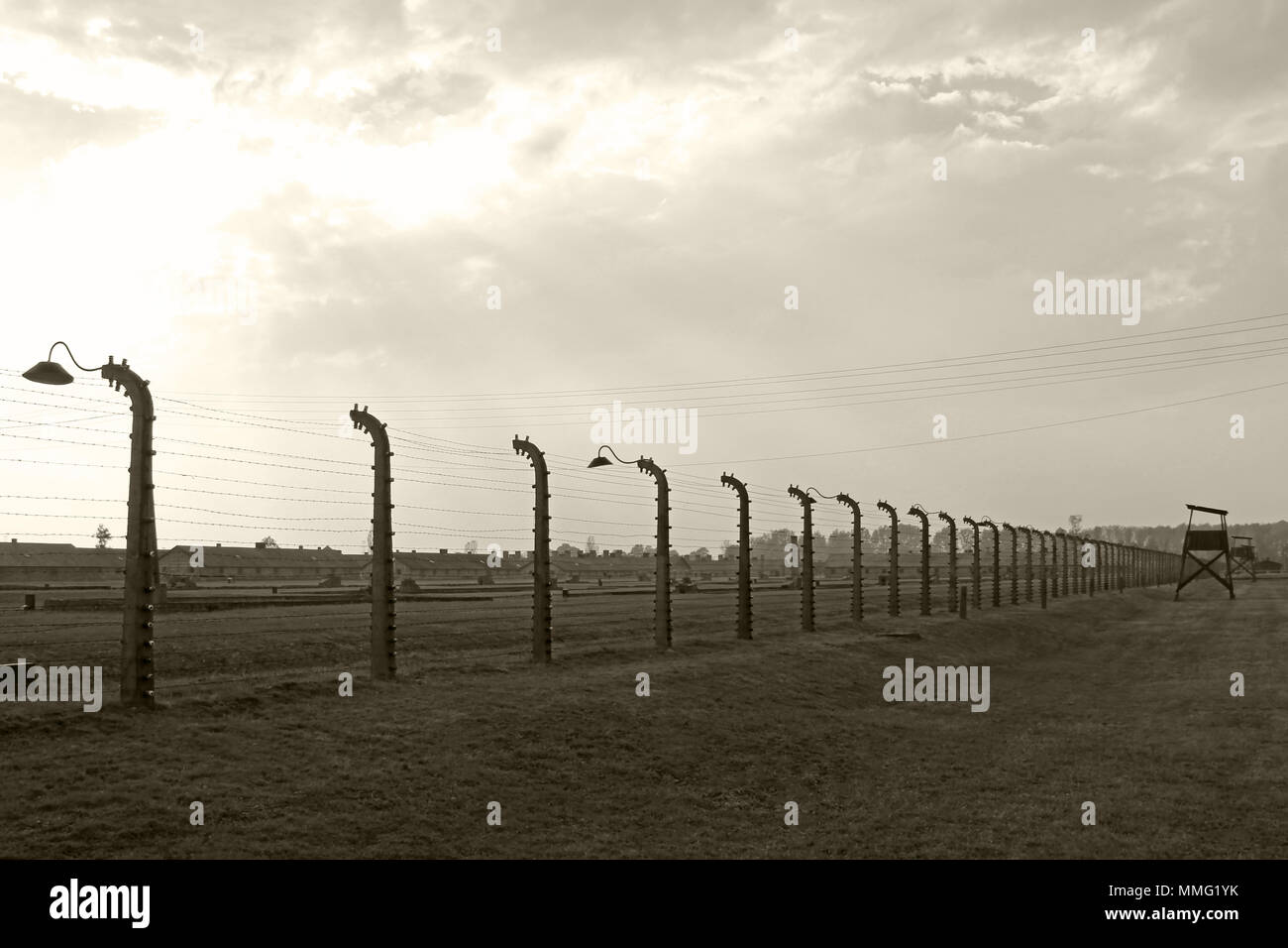 AUSCHWITZ, POLAND, OCTOBER 12, 2013: Fence and watchtower at concentration camp at Auschwitz Birkenau KZ, black white and beige duplex processing photography, Poland - Stock Image