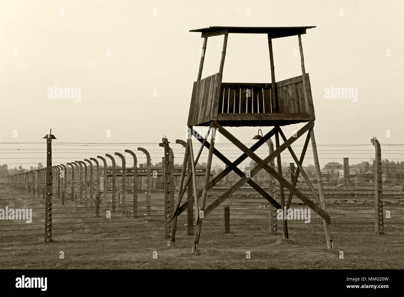 AUSCHWITZ, POLAND, OCTOBER 12, 2013: Watchtower and fence at concentration camp at Auschwitz Birkenau KZ, black white and beige duplex processing photography, Poland - Stock Image