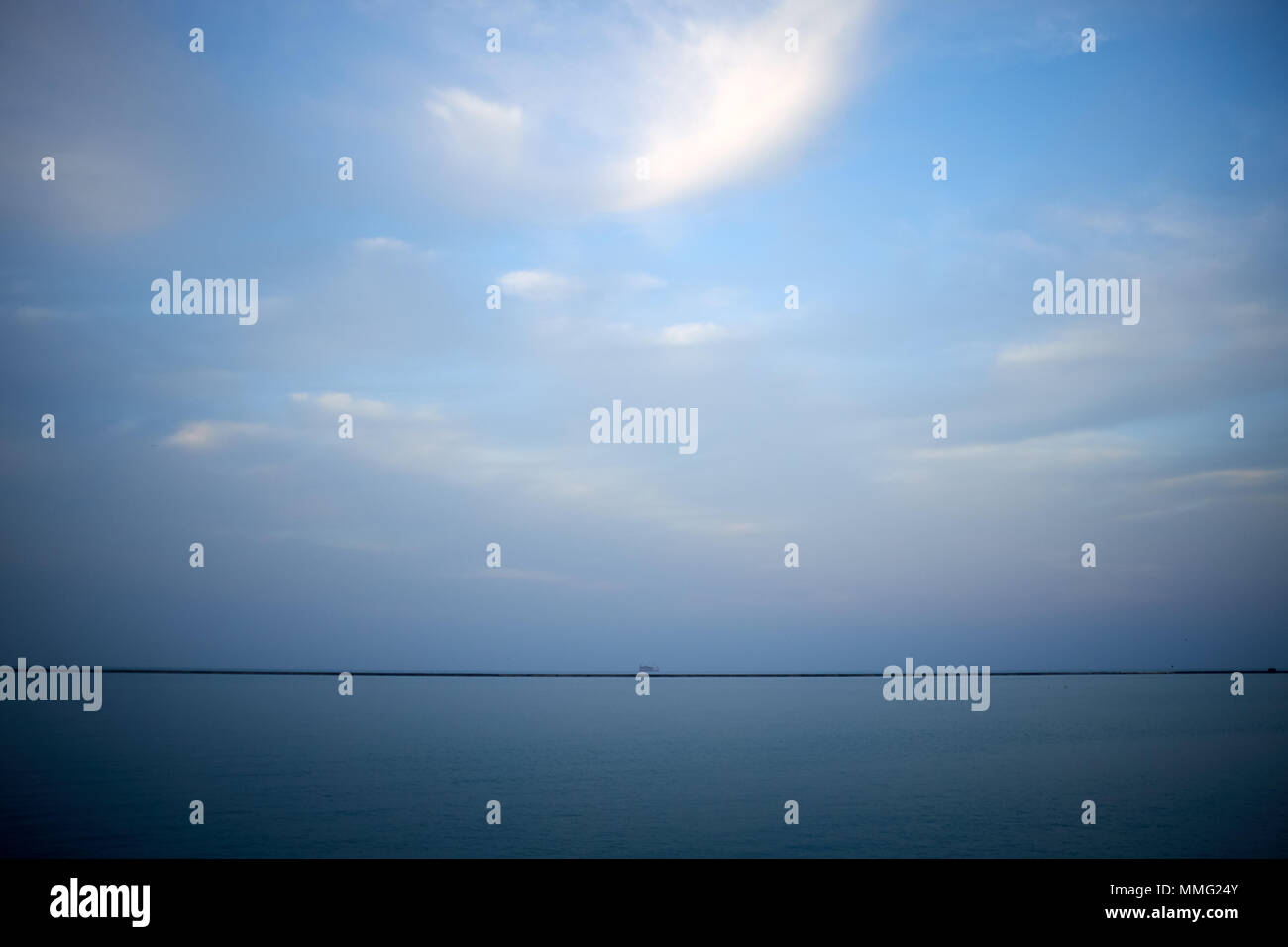 Minimalist landscape on Lake Michigan, Illinois with a distant view of the breakwater at Navy Pier, Chicago on the horizon viewed over calm blue water - Stock Image