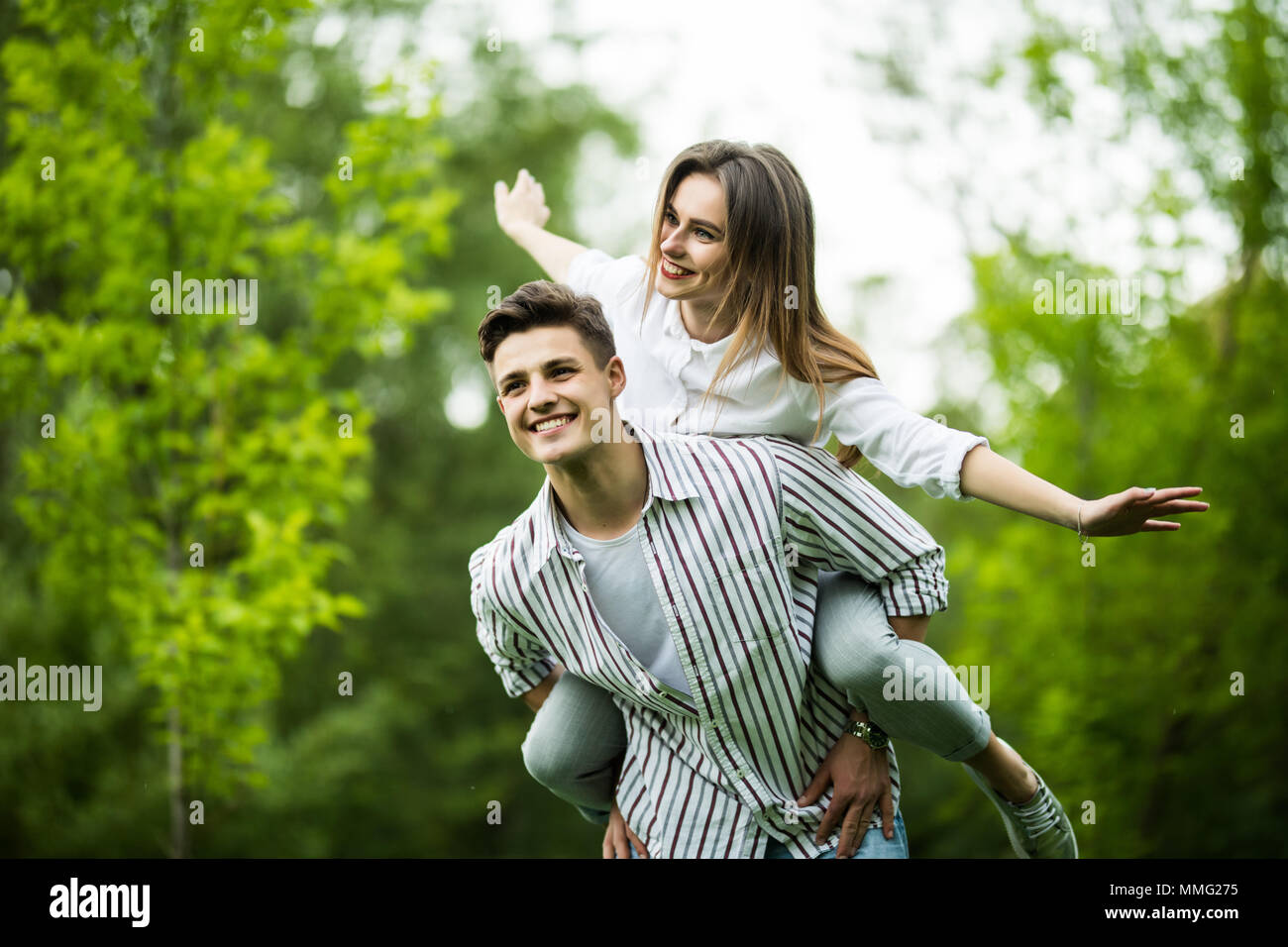 Cute sweet partner piggybacking his lady, she rides him, they are well dressed, excited, lovely, with spread hands - Stock Image