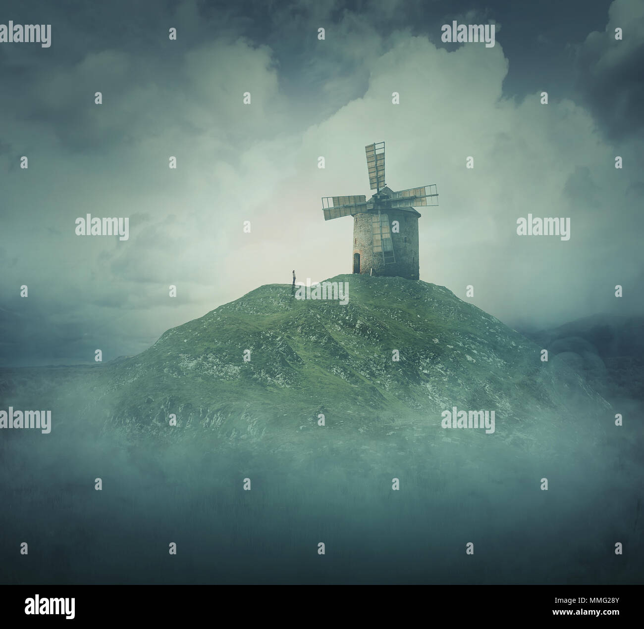 Scenery view as a wander girl silhouette stand in front of an old windmill on the top of a hill surrounded by fog and clouds. Life journey concept, st - Stock Image