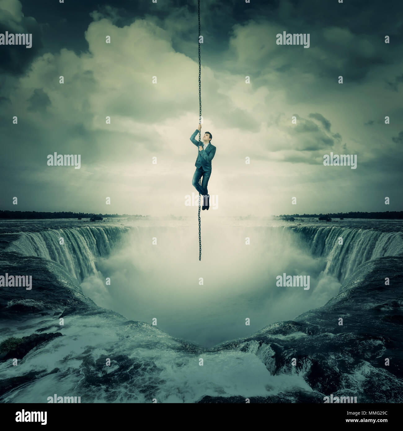 Businessman salvation, surviving the storm buiness concept as a scared man hanging on a chain escape above a waterfall, trying to climb up. Risk symbo - Stock Image