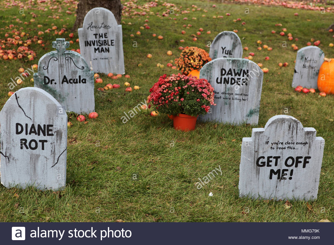 a halloween display featuring tombstones with funny text on a lawn