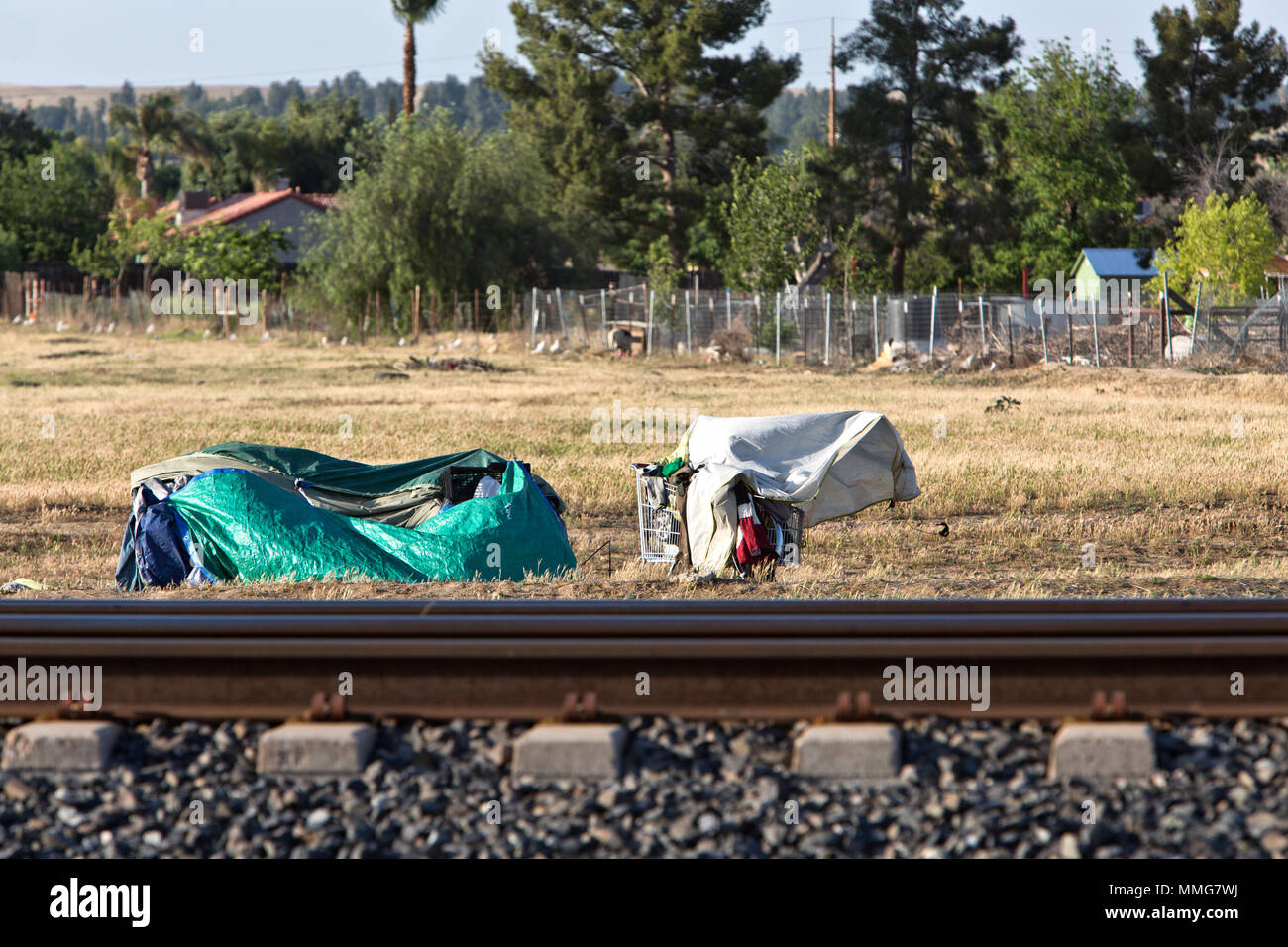 Homeless camp, railroad tracks, rural Kern County, fenced subdivision in background,  California. - Stock Image
