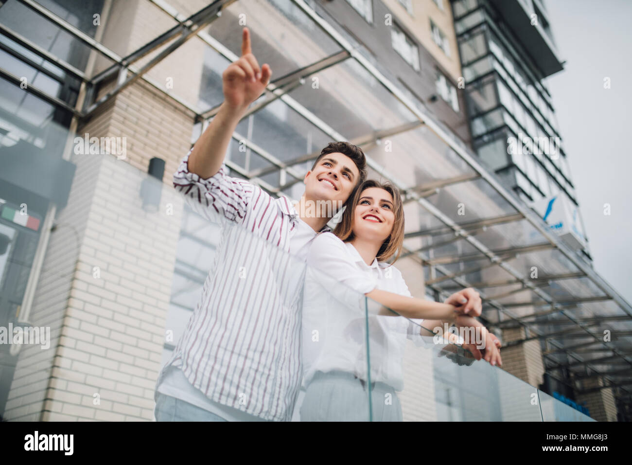 Real estate and family concept. Young couple on front of new big modern house construction pointed side - Stock Image