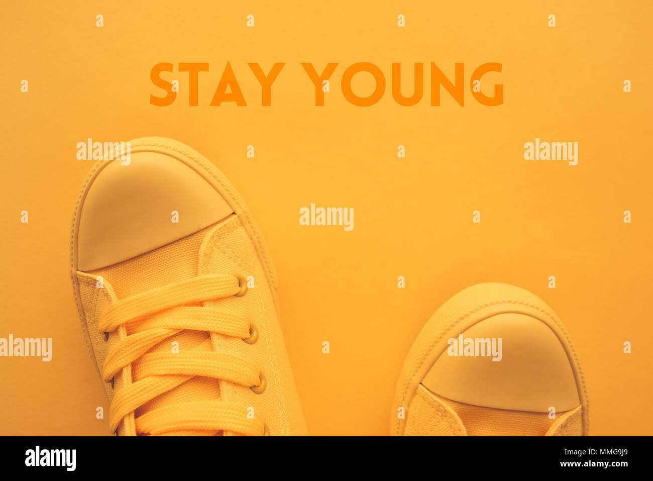 Stay young concept with top view of teenager's feet in stylish yellow sneakers - Stock Image