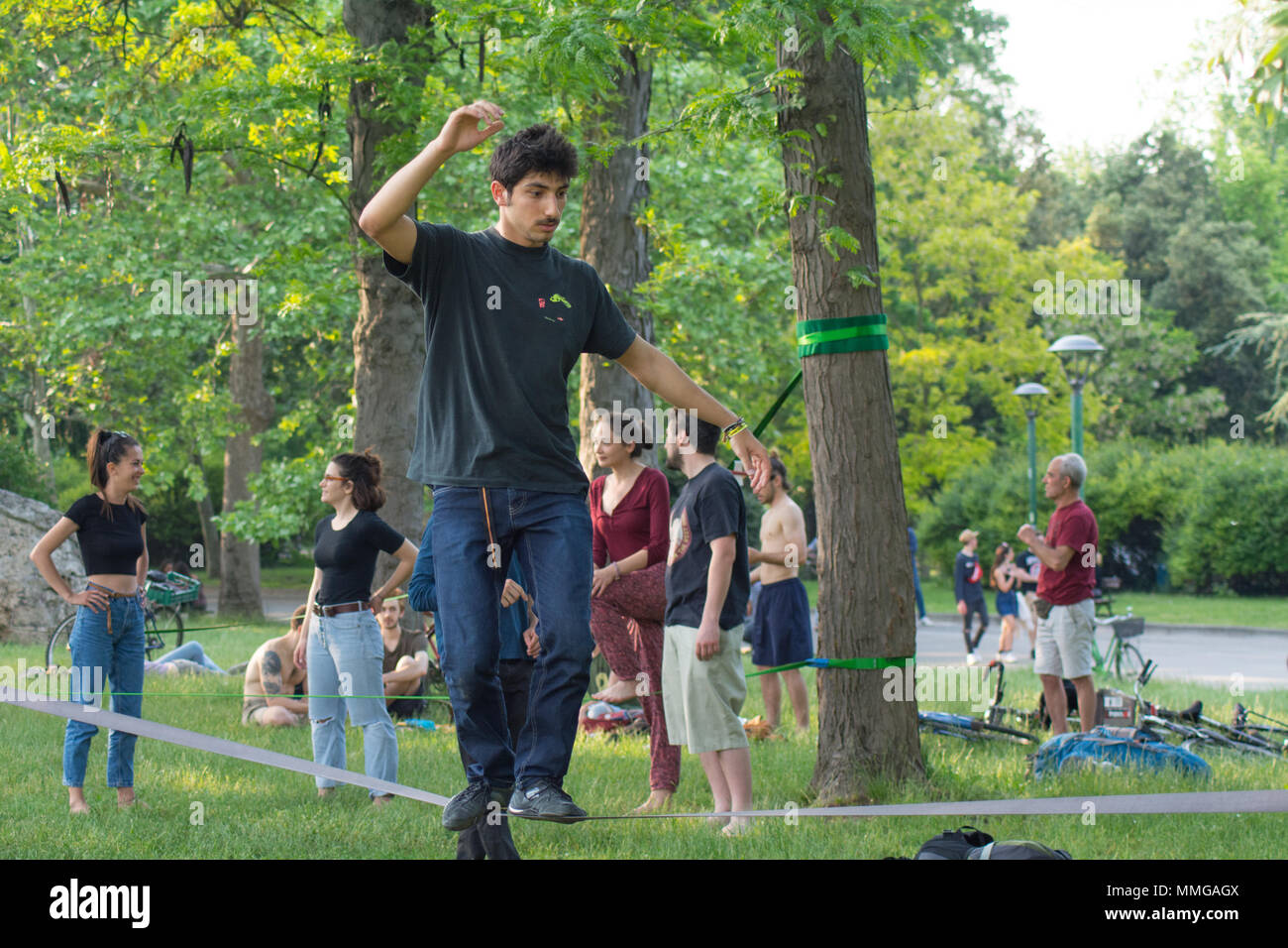front view of a black haired young man on the slackline, slacklining - Stock Image