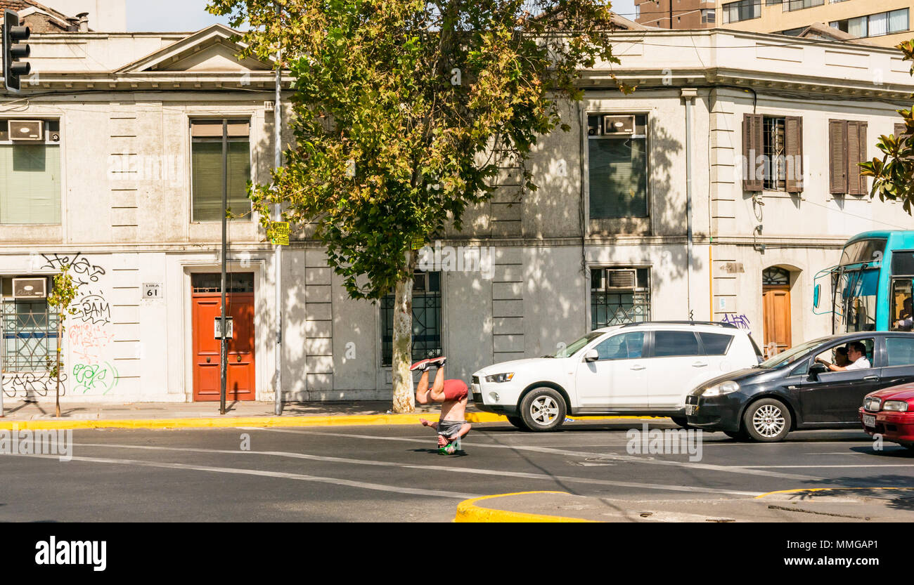 Man hoping to earn money by performing twirls on his head in front of traffic stopped at lights, Santiago, Chile, South America - Stock Image