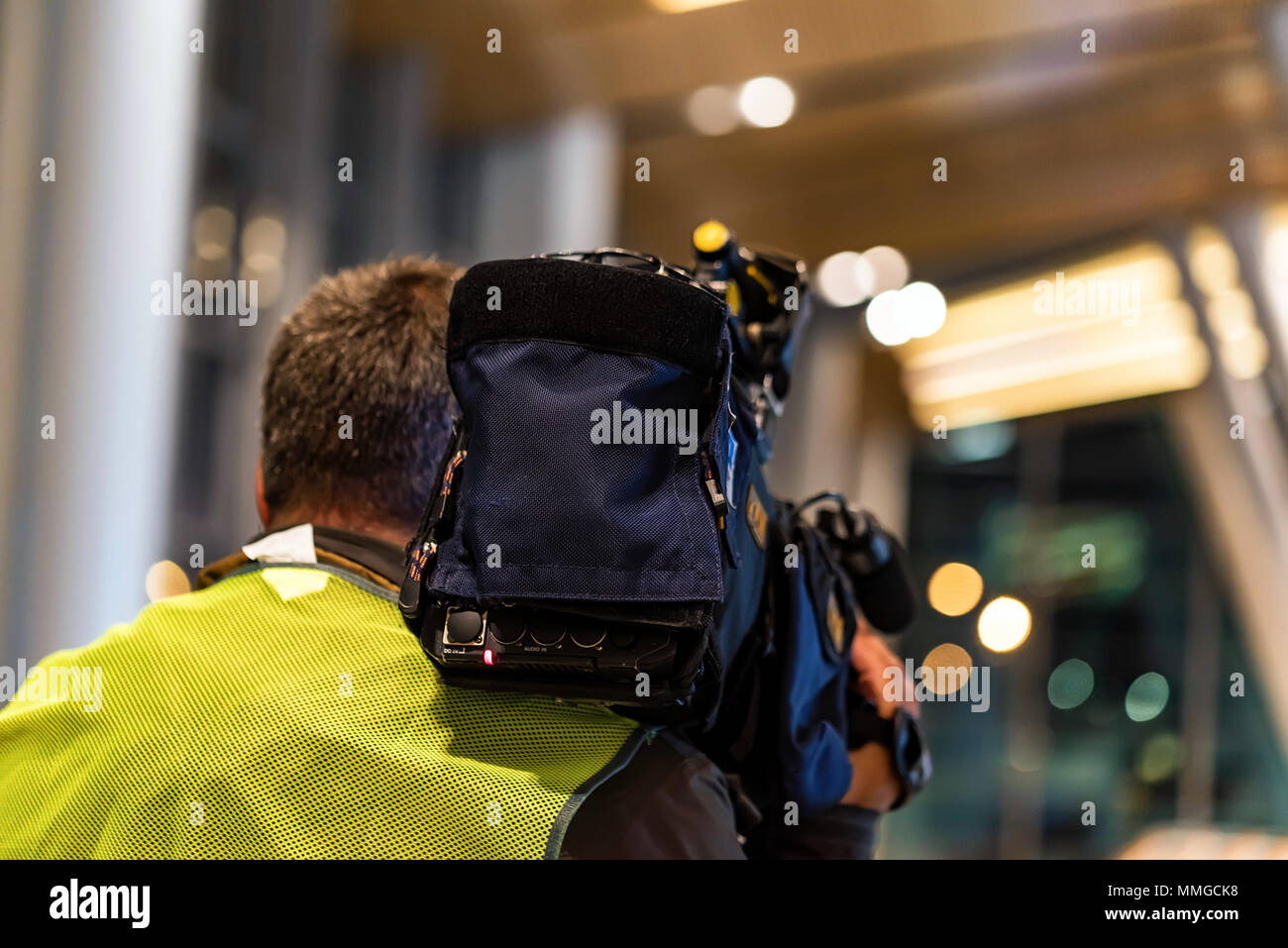 Back view cameraman filming news indoors - Stock Image