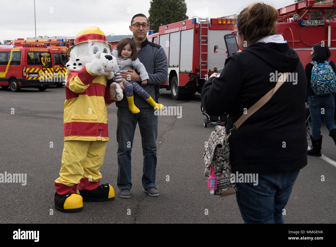 """Members of the Kaiserslautern Military Community take a photo with Sparky the fire dog during the Fire Prevention Week open house on Ramstein Air Base, Germany, Oct. 7, 2017. Fire Departments from Ramstein Village, Landstuhl, Carlsberg, and Technical Relief Foundation (THW) Kaiserslautern, participated in the parade and open house. This year's theme, """"Every second counts, plan two ways out!"""" encourages families to have more than one exit plan in case of an emergency. (U.S. Air Force photo by Airman 1st Class Devin M. Rumbaugh) - Stock Image"""
