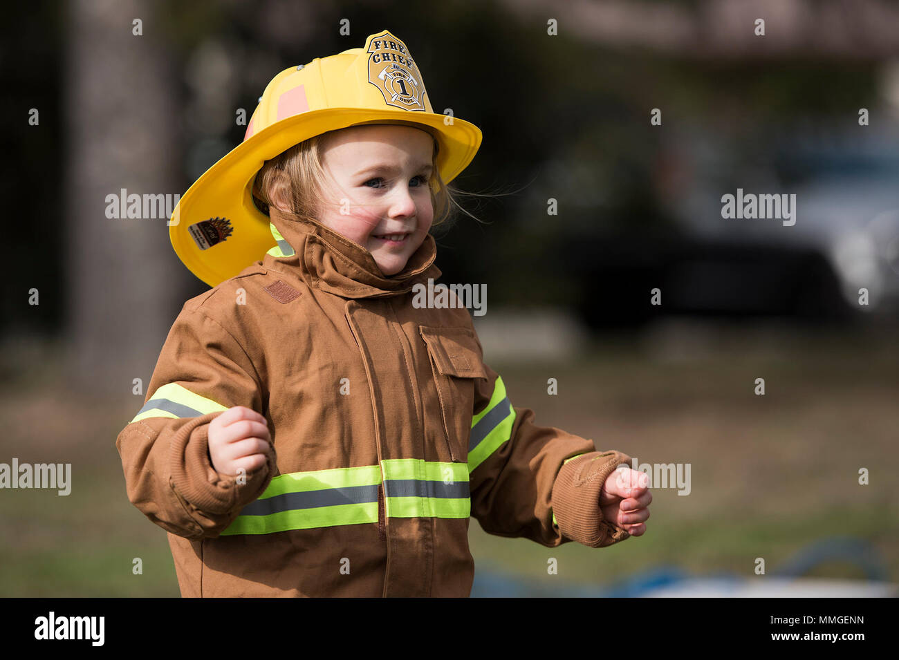 """A child from the Kaiserslautern Military Community runs a child fireman's course during the Fire Prevention Week open house on Ramstein Air Base, Germany, Oct. 7, 2017. The course included a fire hose drag, litter carry and forcible entry challenges. Fire Departments from Ramstein Village, Landstuhl, Carlsberg, and Technical Relief Foundation (THW) Kaiserslautern, participated in the parade and open house. This year's theme, """"Every second counts, plan two ways out!"""" encourages families to have more than one exit plan in case of an emergency. (U.S. Air Force photo by Airman 1st Class Devin M. R - Stock Image"""