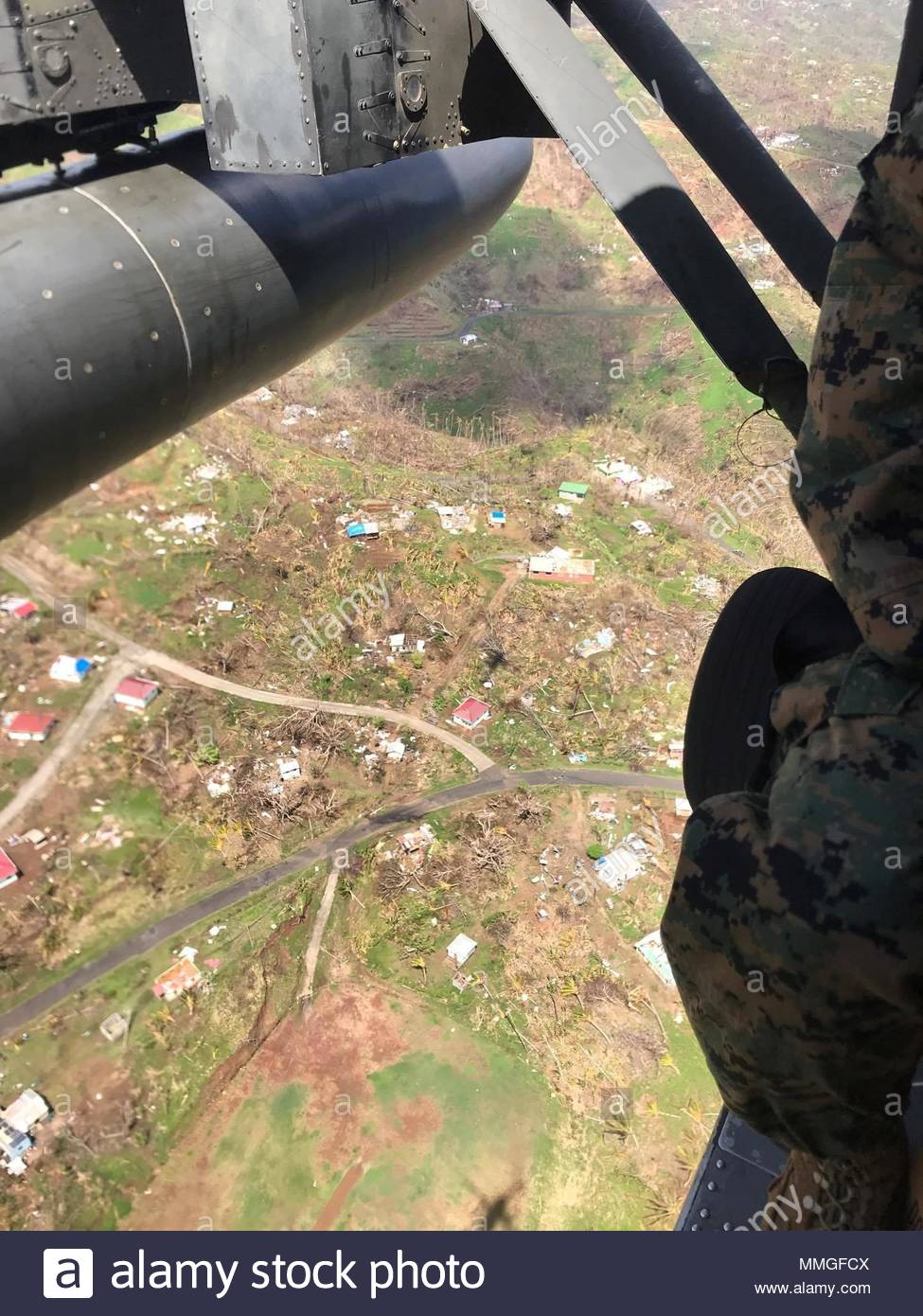 U.S. service members fly over the Caribbean island of Dominica, Oct. 9, 2017. The island was devastated by Hurricane Maria, a Category 5 storm that made landfall Sept. 19, 2017, spurring support from the Joint Base Lewis-McChord community, as well as military installations across the globe. (Courtesy Photo) - Stock Image
