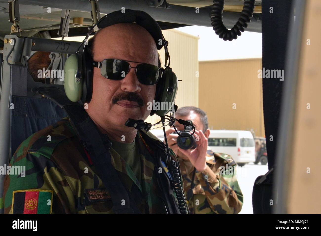 KANDAHAR AIRFIELD (May 8, 2018) -- Maj. Gen. Mohammad Shoaib, Afghan Air Force commander, prepares for a flight in a UH-60 Black Hawk May 8, 2018, Kandahar Air base, Afghanistan. The lead aircraft for the flight was operated by Afghan air crew members who had graduated from Mission Qualification Training earlier that day. (U.S. Air Force photo/1st Lt. Erin Recanzone) - Stock Image