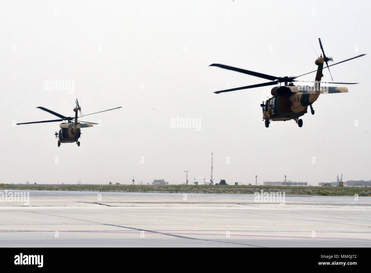 KANDAHAR AIRFIELD (May 8, 2018) -- Two UH-60 Black Hawks, one operated by Afghan air crew members, the other by U.S. advisors, take to the sky for their first flight shortly after a Mission Qualification Training graduation ceremony May 8, 2018, Kandahar Air base, Afghanistan. Thirty one individuals graduated during the ceremony making them the first fully qualified UH-60 Afghan air crew members. (U.S. Air Force photo/1st Lt. Erin Recanzone) - Stock Image