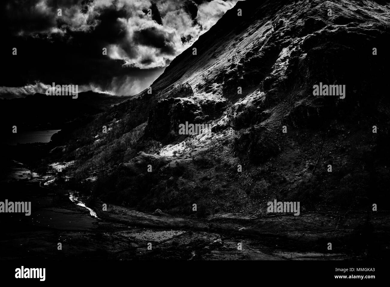 Dark and moody black and white photo of dappled light on the Eastern side of Mount Snowdon on a summer's day Stock Photo