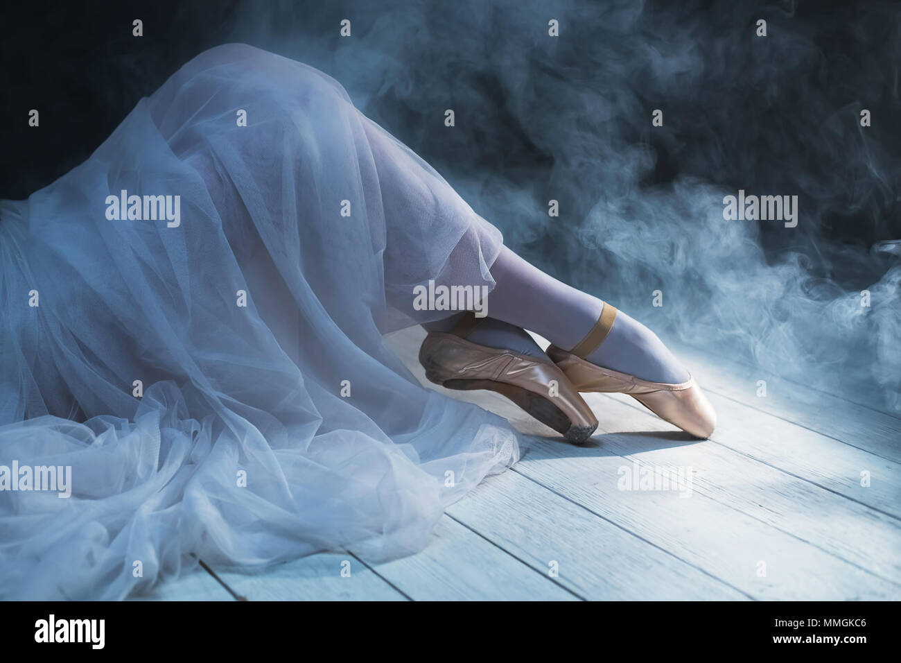 The feet of ballerina in the smoke. Beautiful classic dance background. - Stock Image