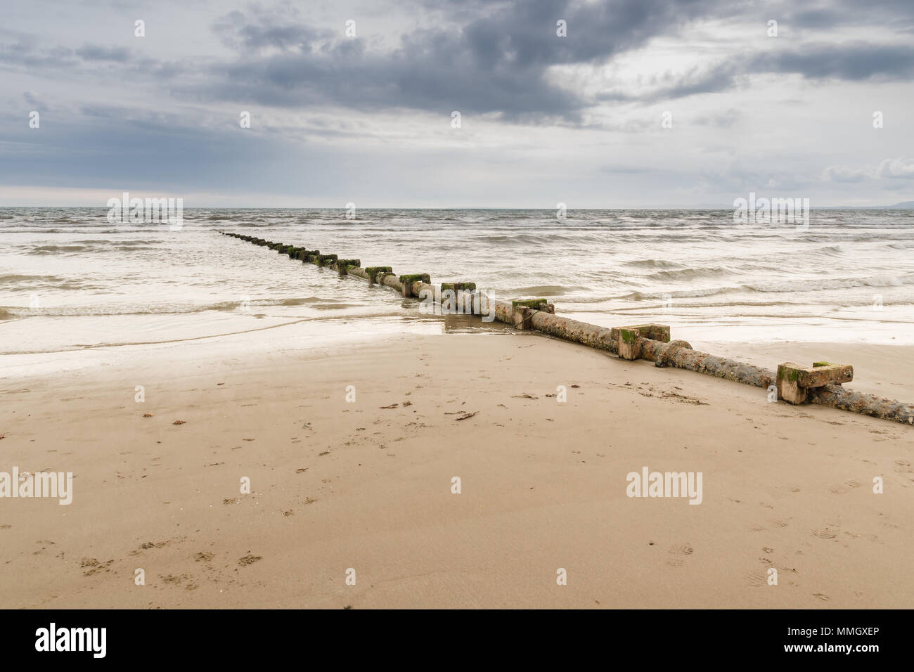 Sewage or waste water discharge pipe leading out to sea on Harlech beach North Wales Stock Photo