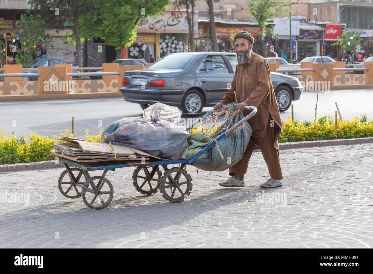SHIRAZ, IRAN - APRIL 25, 2015: an unidentified man pushes a cart in the streets of Shiraz, Iran - Stock Image