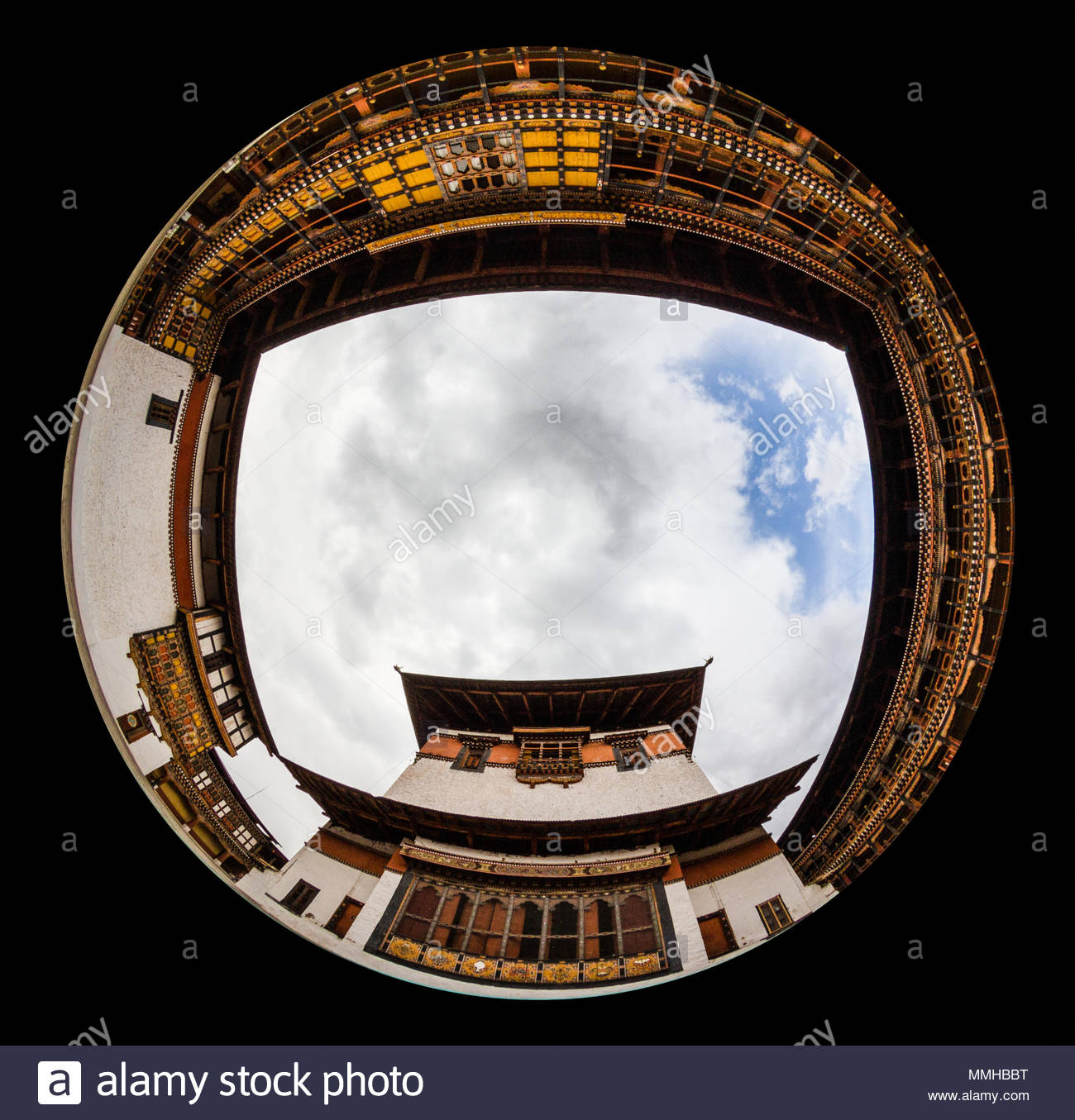 Fisheye lens photography lends itself naturally to tight areas with subjects all around. In this case, the image is taken looking up at the temple inside the Rinpung Dzong in Paro, Bhutan. Dzongs were once the fortresses that housed local rulers before Bhutan became a united country. Today they are typically used for both regional government activities and by Buddhist monks as a monastery. As Buddhism is the official religion of Bhutan, the mixing of the two uses is quite natural. - Stock Image