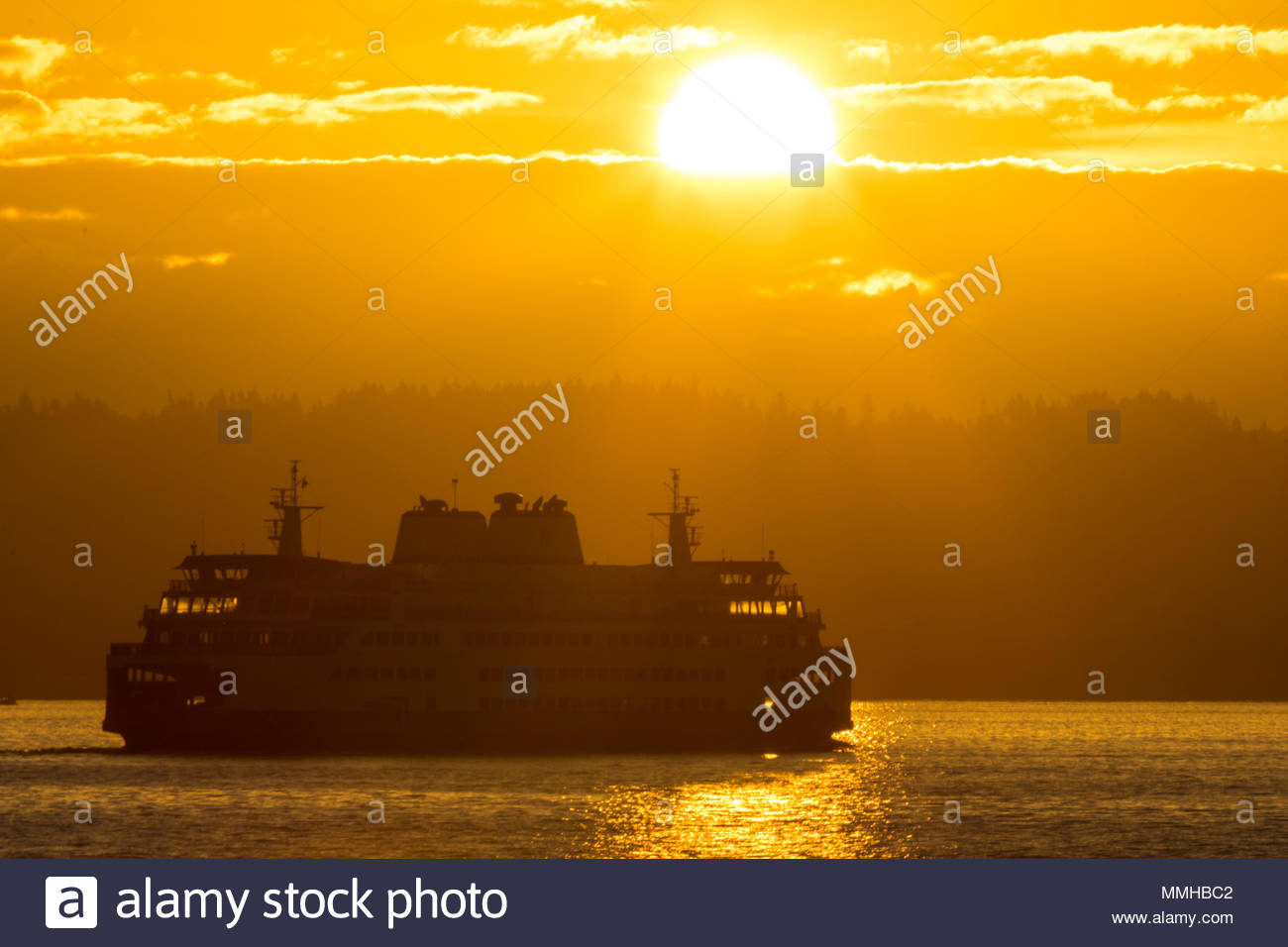 A Washington State Ferry boat is seen in front of the sun rise over the Cascade Mountains of Washington State - Stock Image