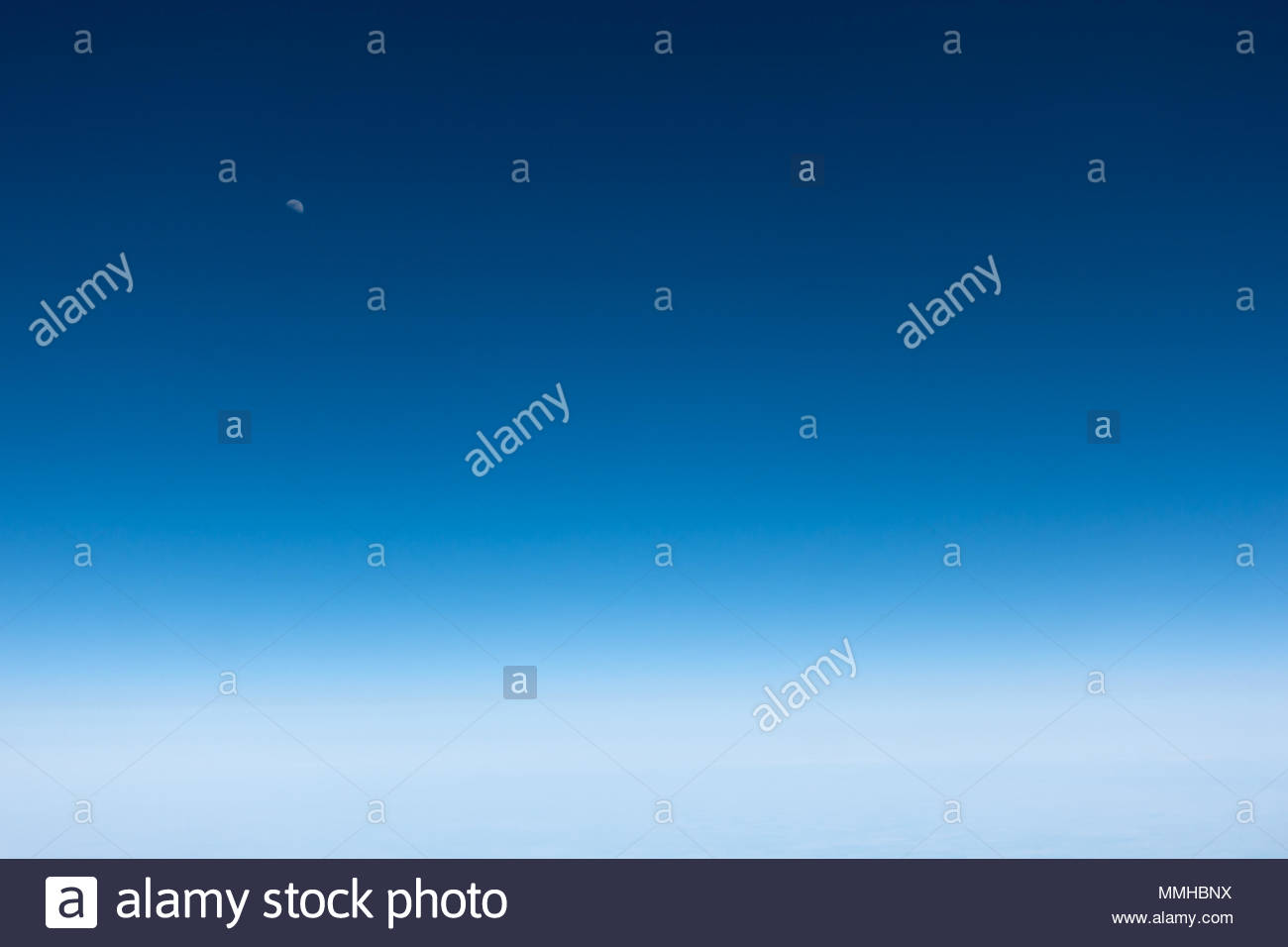 A half moon is seen above thin clouds, as seen from a commercial airliner - Stock Image