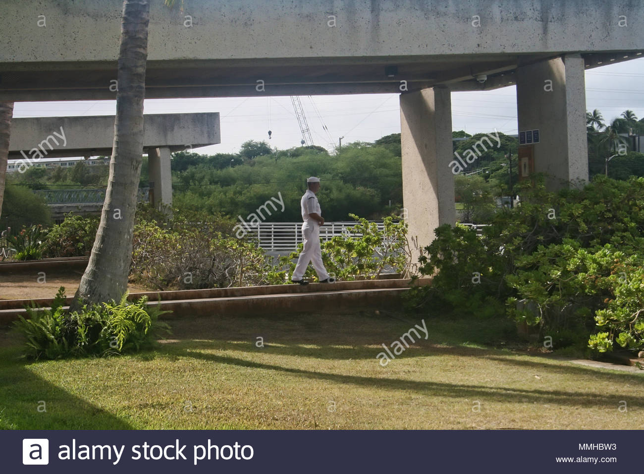 A sailor walks along the grounds of the visitor center at Pearl Harbor in Hawaii. Stock Photo