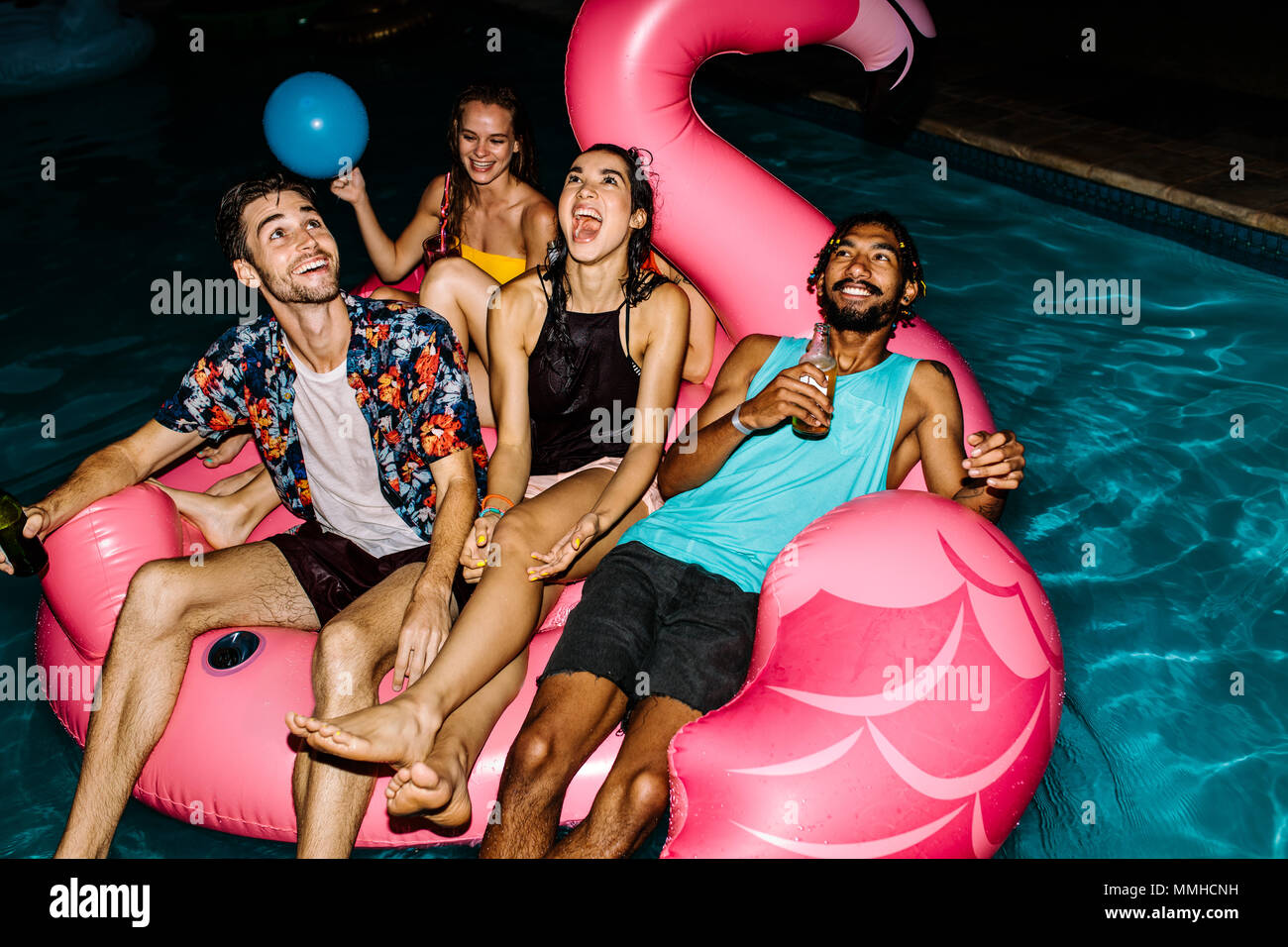 Multiracial group of friends having party in a swimming pool. Happy young people chilling on air mattress in pool. Stock Photo