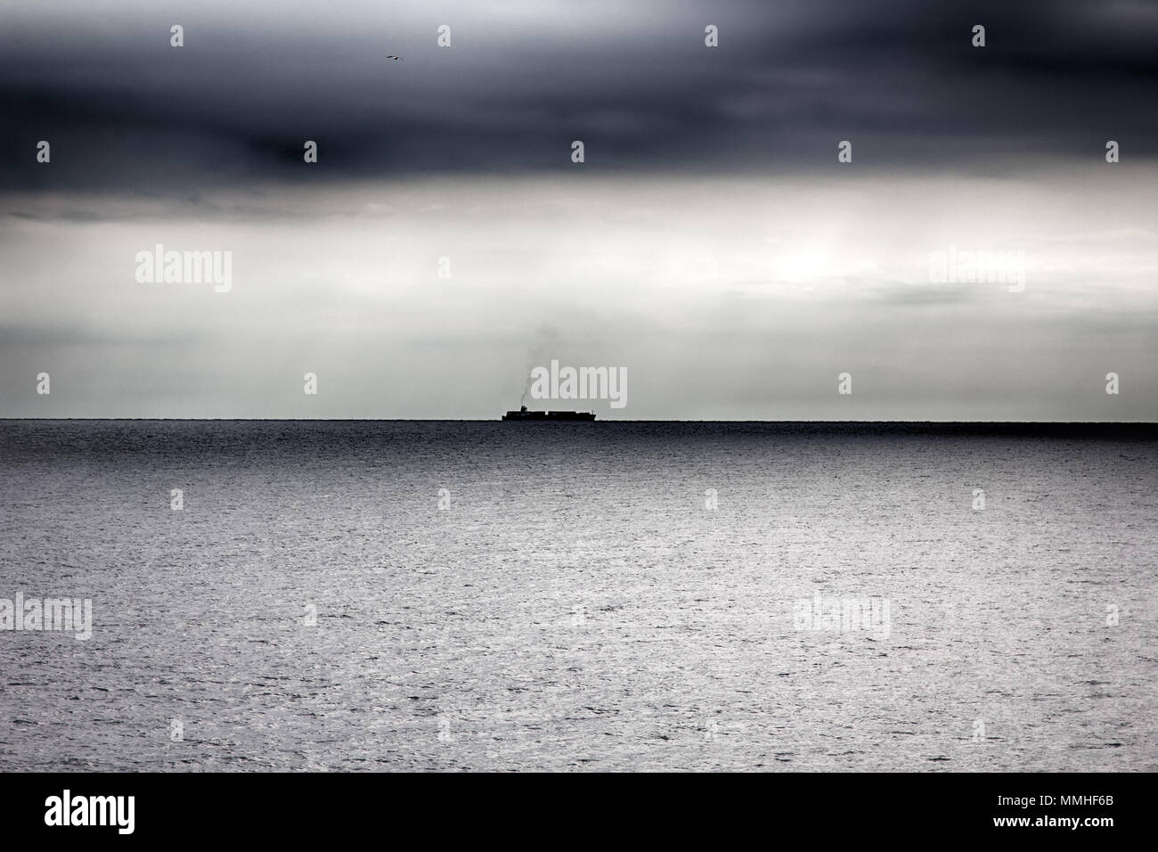 container ship in vastness of the Mediterranean sea, wintertime and dreary winter sea, high-sea shipping; maritime trade; sea shipping; seaborne trade Stock Photo