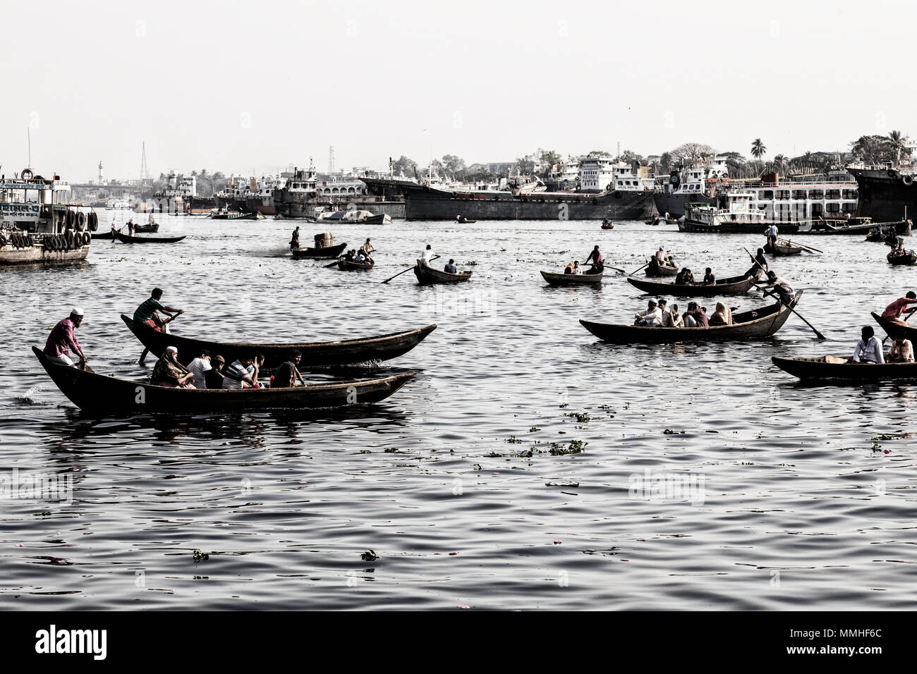 Dhaka, Bangladesh, February 24 2017: Small rowboats serve as taxi between the two river banks on the Buriganga River in Dhaka Bangladesh (Vintage Phot - Stock Image